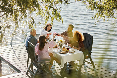 Friends having dinner on jetty at a lake clinking wine glasses - ZEDF03554