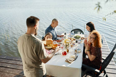 Friends having dinner at a lake with man serving cheese platter - ZEDF03572
