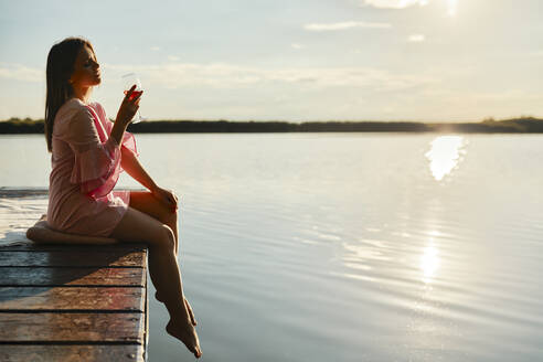 Young woman with a glass of wine sitting on jetty at a lake at sunset - ZEDF03578