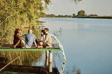 Friends having picnic on jetty at a lake - ZEDF03590