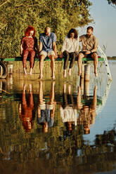 Friends reflected in water sitting on jetty at a lake - ZEDF03593