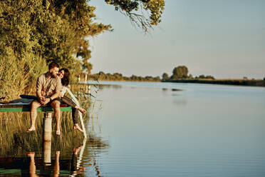 Couple reflected in water sitting on jetty at a lake - ZEDF03599