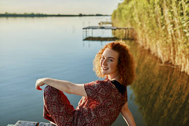 Portrait of smiling redheaded young woman sitting on jetty at a lake at sunset - ZEDF03608