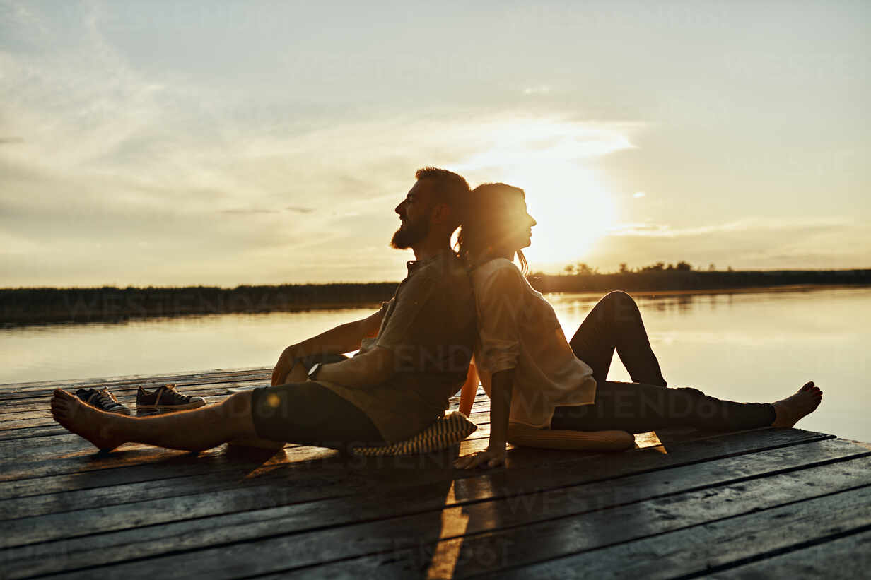 Couple sitting back to back on jetty at a lake at sunset - ZEDF03611 - Zeljko Dangubic/Westend61