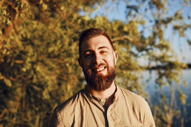 Portrait of smiling man at a lake at sunset - ZEDF03614