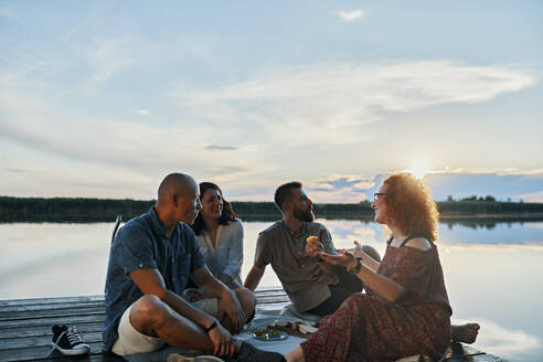 Friends having picnic on jetty at a lake at sunset - ZEDF03617