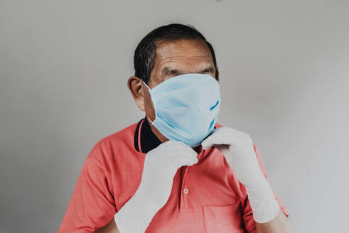 Senior man wearing protective mask and gloves - DSIF00008