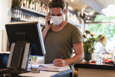 Restaurant manager with protective mask using computer and smartphone for reservation - DIGF12752