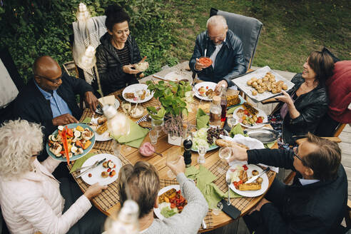 High angle view of senior male and female friends enjoying dinner at dining table during back yard garden party - MASF19002