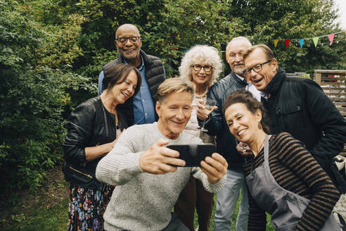 Smiling senior man taking selfie with female and male friends during garden party at back yard - MASF19005