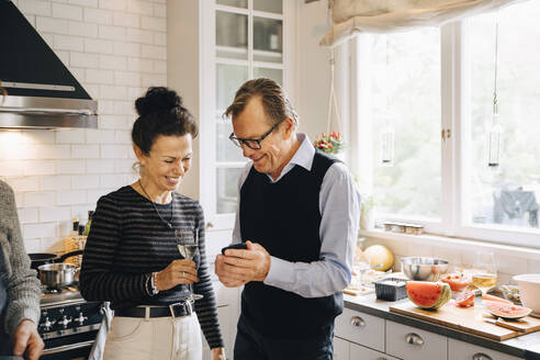 Smiling man and woman sharing smart phone while standing in kitchen - MASF19014