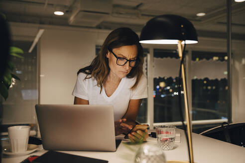 Confident female entrepreneur using smart phone while sitting with laptop at illuminated desk in workplace during night - MASF19405