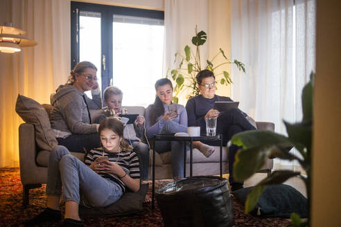 Family using wireless technologies in living room while relaxing on sofa at modern home - MASF19429