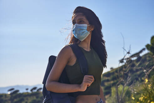 Young woman with long brown hair standing on hill carrying backpack and wearing face mask during Coronavirus Crisis. - CUF55756