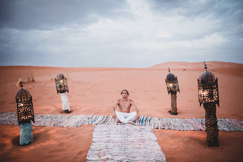 Young shirtless man in white trousers sitting on colorful carpets in desert of Morocco surrounded by decorative lanterns on background of blue cloudy sky - ADSF00205