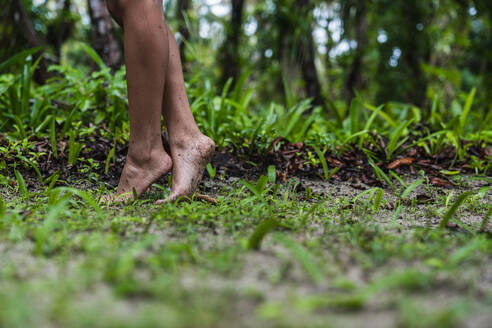 Side view of crop legs of barefooted woman on land in green forest in Bocas del Toro Islands, Panama - ADSF00292