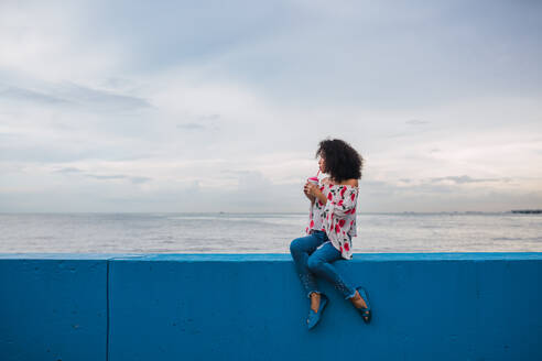 Ethnic stylish woman enjoying delicious drink in cup sitting on blue fence of seafront, Panama city - ADSF00304