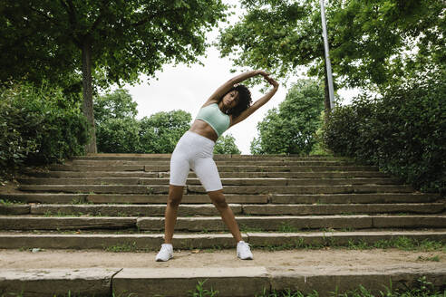 Athletic young woman stretching arms on steps - XLGF00339