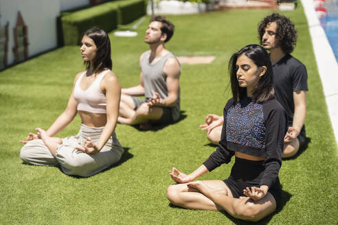 Young mala and female friends meditating while practicing yoga on grass at back yard during sunny - JSMF01621