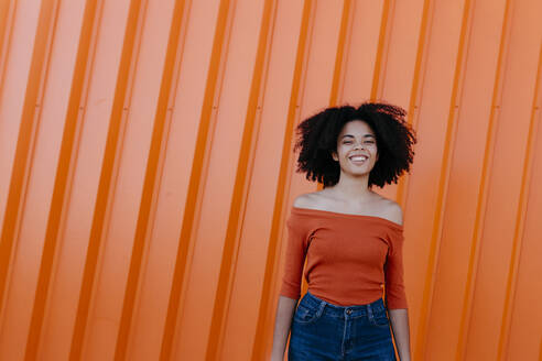 Cheerful young afro woman standing against orange metal wall - TCEF00913