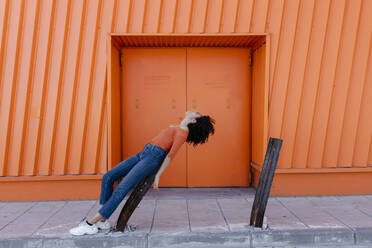 Young woman leaning on damaged metal by orange door - TCEF00916