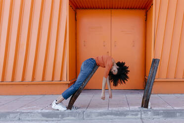 Young afro woman leaning on metal by orange door - TCEF00919