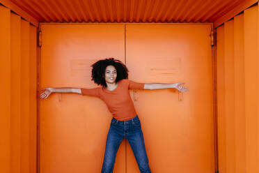 Smiling young woman standing with arms outstretched against orange metal door - TCEF00922