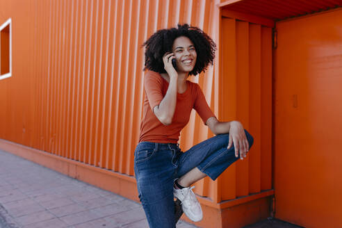 Cheerful young woman talking on smart phone against orange structure - TCEF00925