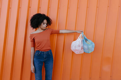 Young woman holding bags against orange wall - TCEF00928