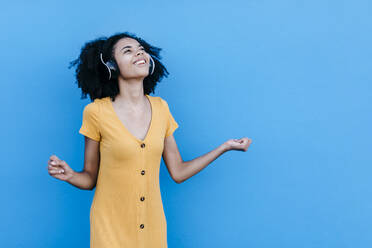 Happy young afro woman enjoying while listening music through headphones against blue wall - TCEF00931