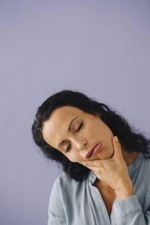 Close-up of woman with eyes closed making face against purple background - JOSEF01387
