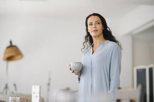 Thoughtful female owner holding coffee mug while standing in cafe - JOSEF01390