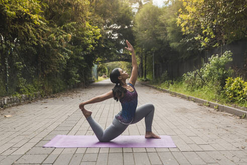 Young woman exercising on mat amidst plants at park - DSIF00011