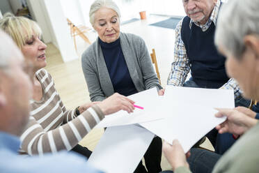 Group of seniors attending therapy group in retirement home, using sheets of paper - WESTF24607