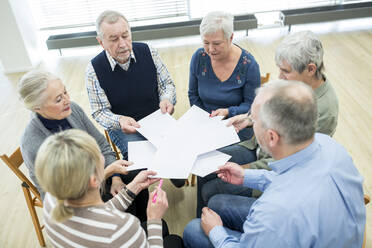 Group of seniors attending therapy group in retirement home, using sheets of paper - WESTF24610