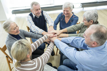 Group of active seniors stacking hands, symbolizing solidarity - WESTF24613