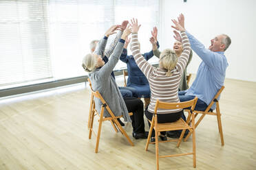 Group of seniors practicing chair gymnastics with instructor  in retirement home - WESTF24622