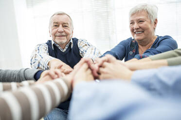 Group of active seniors stacking hands, symbolizing solidarity - WESTF24628