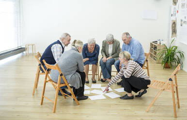 Group of seniors in retirement home evaluating result of group therapy - WESTF24631
