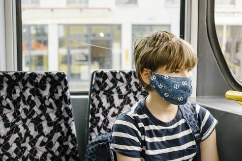 Boy wearing protective mask in tram - MMFF01287