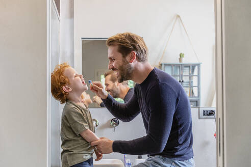 Happy man brushing son's teeth with toothbrush in bathroom at home - EIF00056