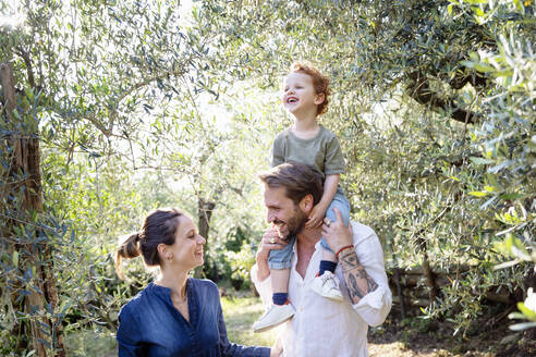 Smiling parents looking at each other while carrying son on shoulders at olive orchard - EIF00062