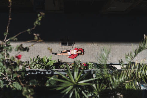 From above shot of girl in red lying down on pavement in bright sunlight looking playful - ADSF00608