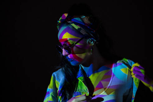 Pretty stylish woman in sunglasses with geometric colorful light on face. - ADSF00857