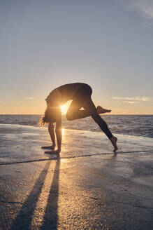 Young woman in Downward Facing Dog Pose near sea - ADSF00896