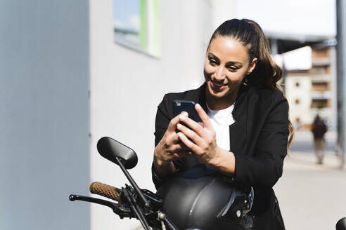 Smiling woman sitting on motorbike and using smartphone - FMOF01017