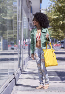 Young woman looking into shop window - PGCF00080