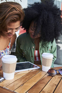 Girlfriends with coffee to go using tablet in cafe - PGCF00089