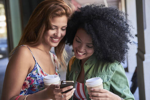 Girlfriends with coffee to go using smartphone - PGCF00095