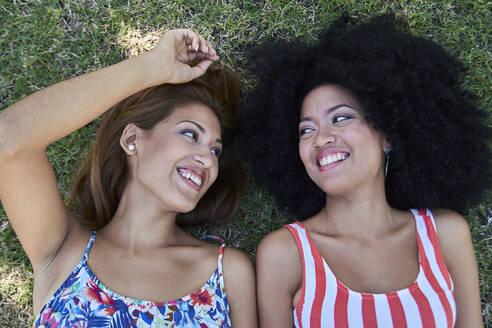 Girlfriends lying on meadow - PGCF00101